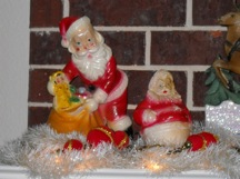 Vintage chalkware Santas on mantel